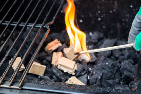 Close up of a blazing match firing up a fire starting brick over a layer of charcoal inside a barbecue fireplace