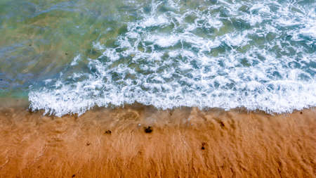 A small wave breaking on the sand of the shore with a beautiful blue sea and brown wet sand Stock Photo