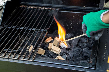 Close up of a hand firing up with a blazing match a fire starting brick over a layer of charcoal inside a barbecue fireplace Stock Photo
