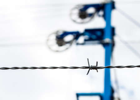 A barbed wire close up with some railroad mechanism in the background Stockfoto