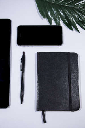 A tablet, cellphone, notebook, pencil and a cool leaf over a white clean desk