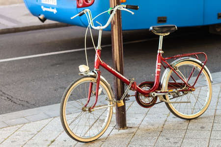 A vintage old red bicycle tied to a post with a chain and a lock in the city Stock fotó