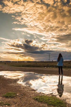 Stunning sunset cloudy scene reflecting in a puddle and a young woman with her back turned contemplating the scene Stockfoto