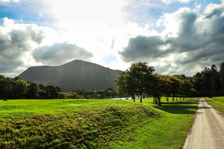 Amazing view of Killarney National Park in Ireland, with trees, a mountain and a cloudy sunny sky