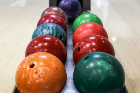 Some colorful bowling balls in the rack of a bowling alley