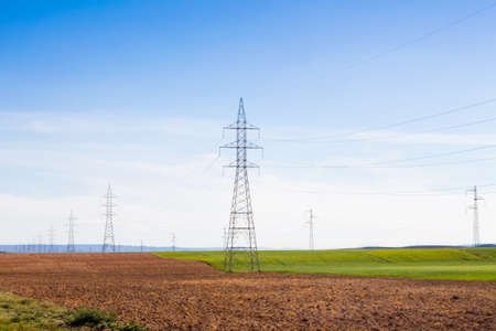 A row of electricity towers in the middle of the countryside, visually impacting the environment Stockfoto - 128781512