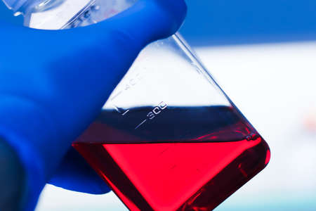 A laboratory technician holding a bottle with red liquid media inside with blue medical sterile gloves Reklamní fotografie