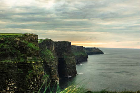 Amazing sunset view of the Cliffs of Moher, in the western side of Ireland, in an overcast cloudy day