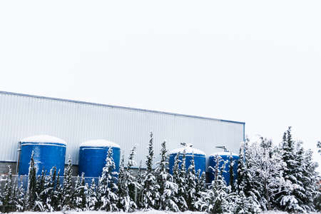 Exterior of a factory in a snowy days, with some tanks of liquid and trees snow covered in winter