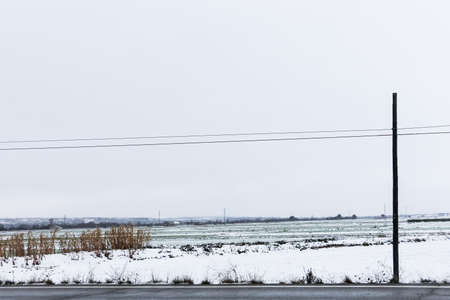 Snow covered fields near a road with a overcast sky in winter