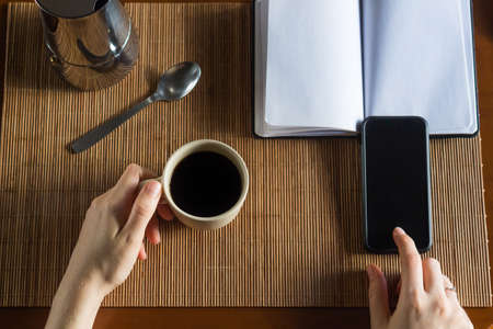 Overhead view of a woman having a cup of coffee in her wooden desk with a notebook, mobile phone, coffee pot and a spoon.