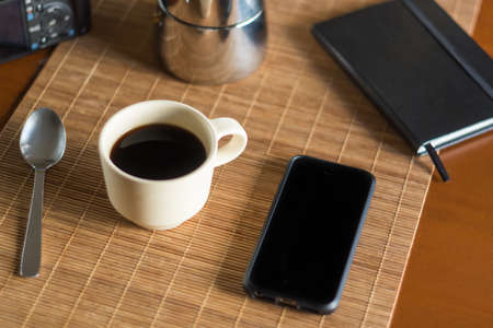 Black screen mobile phone alongside a cup of black hot coffee, a notebook and a metallic coffee pot on a wooden desk