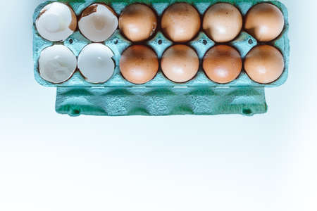 Brown Chicken Eggs And Eggshell inside an egg box On A White Background With Copy Space and natural light. Flat Lay