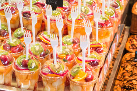fruits cut into plastic cups in a market with plastic fork Stockfoto