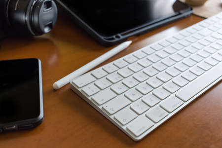 Close up of a white wireless keyboard, with some photographer tools like a digital camera, a tablet, a stylus pen and a mobile phone, all on a wooden desk Stockfoto