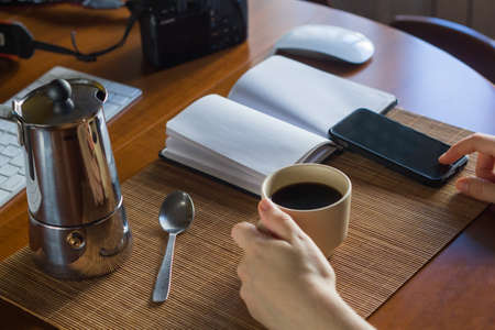 A woman photographer having a cup of coffee in her workspace with a digital camera, mobile phone, notebook, coffee cup and other stuff Stockfoto