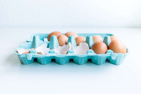 Brown Chicken Eggs And Eggshells inside a blue egg box with natural light