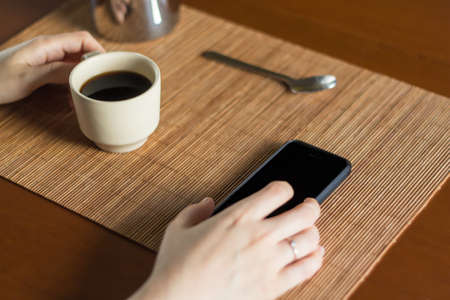 A woman having a cup of hot coffee and looking her mobile phone on a wooden desk with a spoon and a coffee pot
