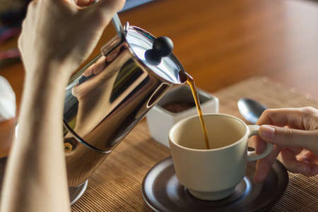 A woman pouring some hot coffee in a cup, on a wooden desk Stockfoto
