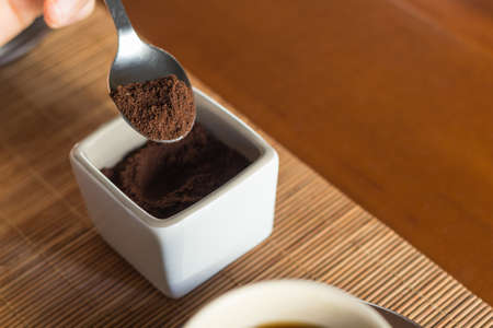Close up of a spoon taking some ground coffee along a cup of coffee in a wooden desk