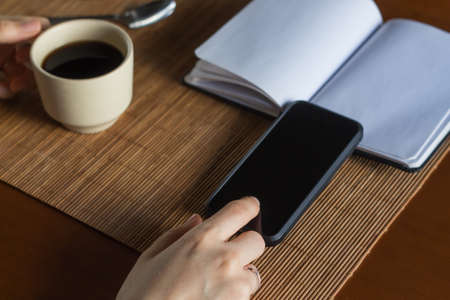 A woman with her smart phone having a cup of coffee and planning business with a notebook