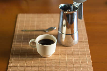 Still life portrait of a hot black coffee cup with a metallic coffee pot and a spoon on a wooden cool clean desk