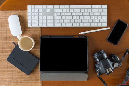 Overhead view of a photographer desk with a camera, tablet, keyboard, mouse, stylus, notebook, mobile phone and an empty coffee cup on a wooden table Stockfoto