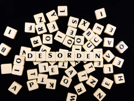 Desorden Word spelled in game tiles with a mess of other tiles in the background Standard-Bild