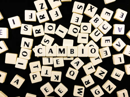 Cambio Word spelled in game tiles with a mess of other tiles in the background