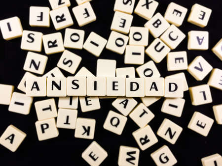 Ansiedad Word spelled in game tiles with a mess of other tiles in the background 스톡 콘텐츠