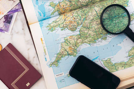 A Smartphone, Passport, smartphone, Magnifying glass, Money, And an umbrella On An England Map for a road trip Stock fotó