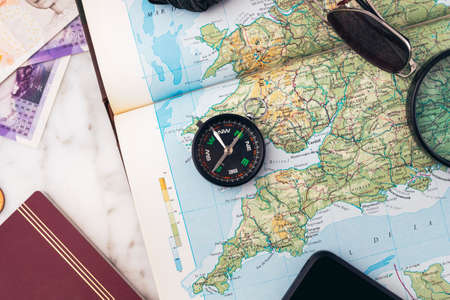 Planning a road trip across England with a compass, smartphone, passport, magnifying glass, sunglasses and money on an England map