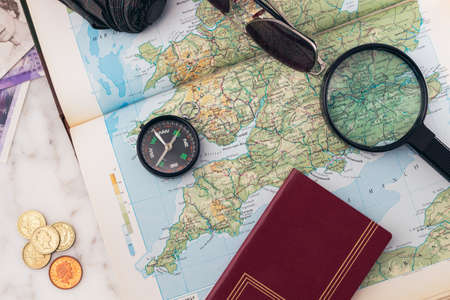 A compass, passport, magnifying glass, sunglasses, umbrella and money on an laid out England map for a trip planning