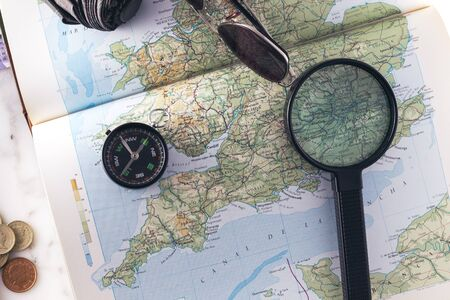 Planning a trip with a compass, magnifying glass, sunglasses, umbrella and money on an England map
