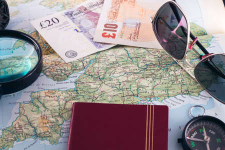 A passport, compass, magnifying glass, sunglasses, umbrella and money on an England map for a road trip