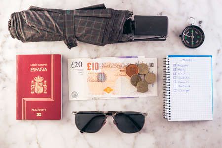 Knolling concept of traveler. Passport, umbrella, money, sunglasses, compass and checklist, all ready to travel to England.