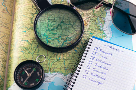 Planning road trip to Kentucky, USA. Compass, sunglasses, checklist and magnifying glass over Louisville, Kentucky. Stock Photo
