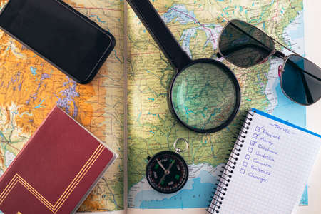 Travel concept. Planning road trip to Kentucky, USA. Compass, sunglasses, checklist, smartphone and magnifying glass on a map.
