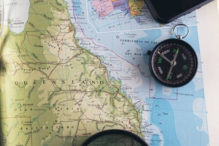 Travel concept. Planning an adventure road trip across the east side of Australia. Compass, smartphone and magnifying glass on a book map. Stock fotó
