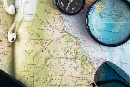 Travel concept. Planning an adventure road trip across the east side of Australia. Compass, smartphone, earphones, sunglasses and magnifying glass on a book map.