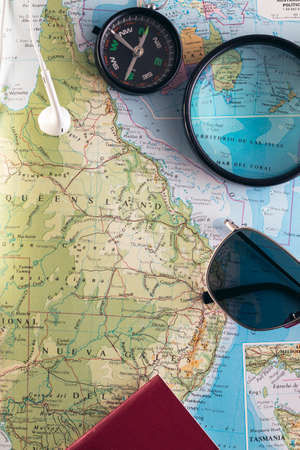 Travel concept. Planning an adventure road trip across the east side of Australia. Compass, passport, sunglasses and magnifying glass on a book map. Vertical image. Stock fotó