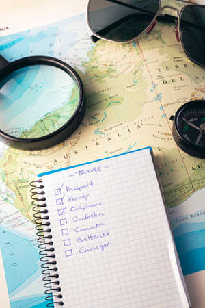 Travel concept. Planning an adventure road trip across the west side of Australia. Sunglasses, compass, magnifying glass and checklist over a map.