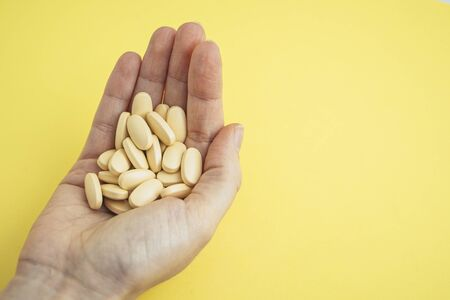 A female hand holding some brown pills on a yellow background