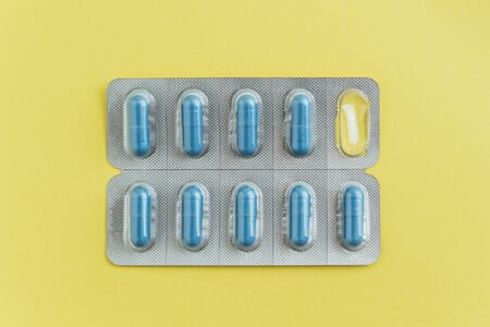 Blister pack of capsules with a pill missing on yellow background. Flat lay