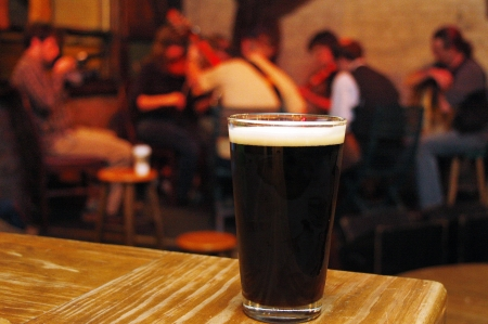 stout: Una pinta de cerveza en un pub irland�s, con el m�sico tocando en el fondo Foto de archivo