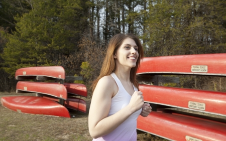 A young woman jogging by red canoes