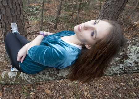 A young woman lying on a tree, relaxing and gazing off