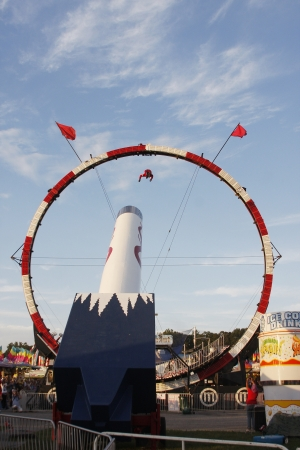 daredevil: A daredevil, human cannonball fired out of cannon and through the center of an amusement ride at the North Carolina Mountain State Fair