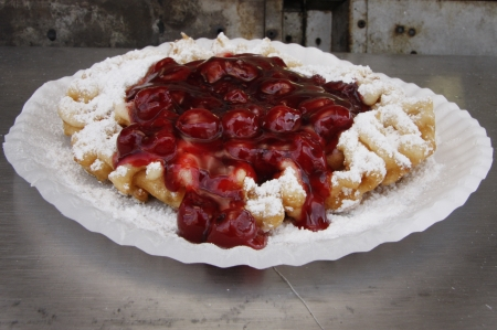 A funnel cake topped with sugar and cherry syrup