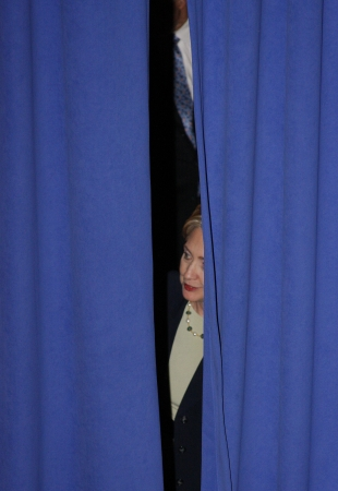 blue curtain: Hillary Clinton peaking out from behind blue curtains at a democratic political rallly in North Carolina Editorial
